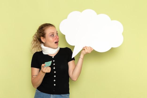 Vorderansicht junge frau, die sich sehr krank und krank fühlt und großes weißes schild hält, das pillen auf der grünen schreibtischkrankheitsmedizin-gesundheitskrankheit hält