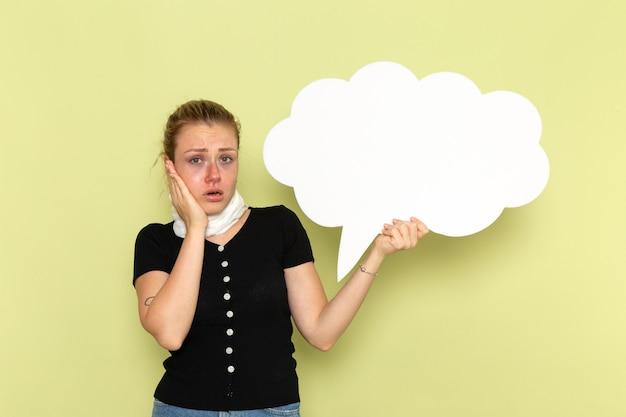 Vorderansicht junge frau, die sich sehr krank und krank fühlt und großes weißes zeichen auf der grünen wandkrankheitsmedizin-gesundheitskrankheit hält