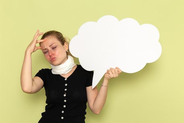 Vorderansicht junge frau, die sich sehr krank und krank fühlt und großes weißes zeichen auf der hellgrünen wandkrankheitsmedizin-gesundheitskrankheit hält