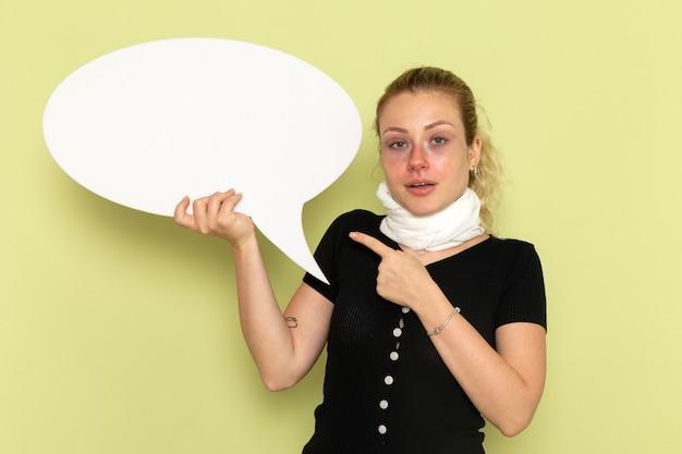 Vorderansicht junge frau, die sich sehr krank und krank fühlt und großes weißes zeichen hält, das auf gesundheitskrankheit der grünen wandkrankheitsmedizin aufwirft