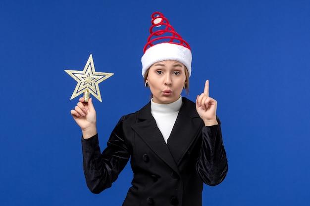 Vorderansicht junge frau, die sternförmiges dekor auf neujahrsferienfrau des blauen schreibtisches hält