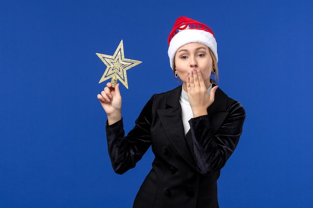 Vorderansicht junge frau, die sternförmiges spielzeug an der neujahrsferienfrau der blauen wand hält