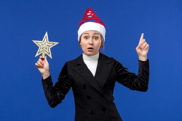 Vorderansicht junge frau, die sternförmiges spielzeug auf einem neuen jahr der blauen schreibtischfeiertagsfrau hält