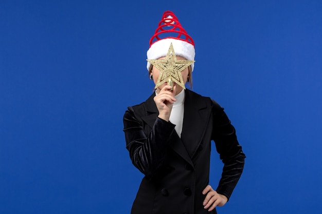 Vorderansicht junge frau, die sternförmiges spielzeug auf neujahrsfeiertag der blauen wand hält