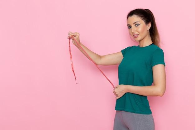 Vorderansicht junge frau, die taillenmaß auf dem hellrosa wandschönheitssport-sporttrainer-training schlank hält