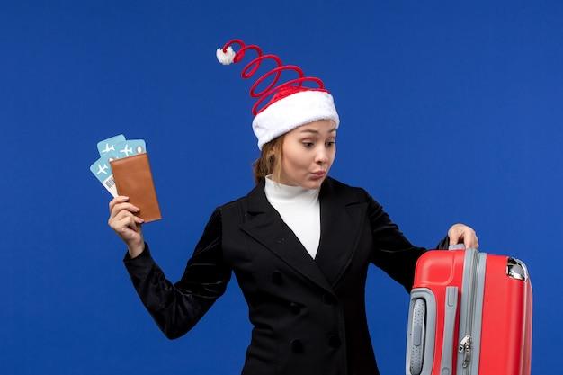 Vorderansicht junge frau, die tickets mit tasche auf blauem hintergrundfeiertagsflugzeugurlaub hält