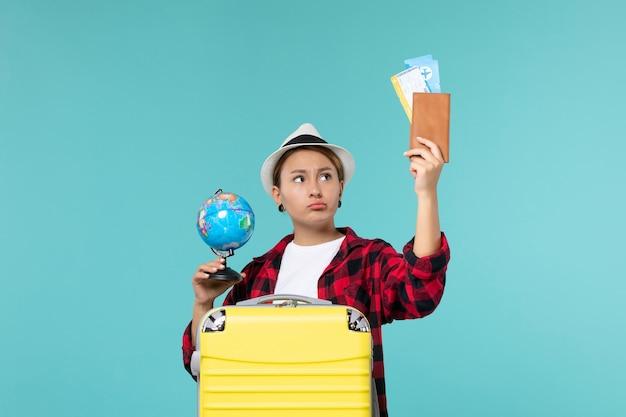 Vorderansicht junge frau, die tickets und globus auf dem blauen raum hält