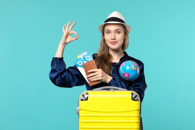 Vorderansicht junge frau, die tickets und globus auf hellblauer hintergrundflugzeug-seeurlaubsreise hält