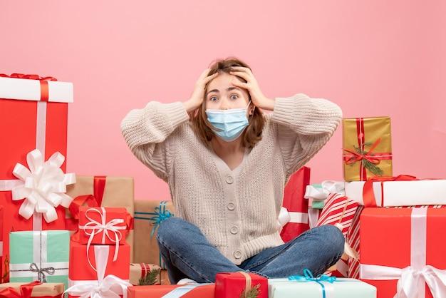 Vorderansicht junge frau, die um weihnachtsgeschenke in der maske sitzt