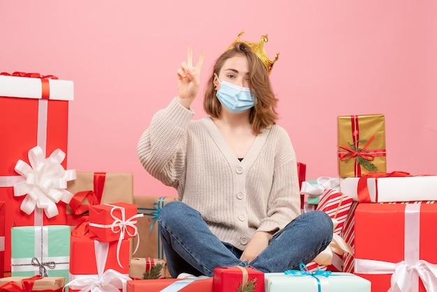 Vorderansicht junge frau, die um weihnachtsgeschenke in der sterilen maske sitzt