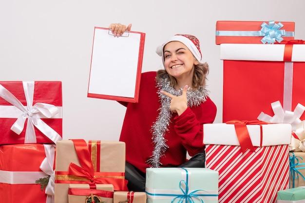 Vorderansicht junge frau, die um weihnachtsgeschenke mit hinweis sitzt