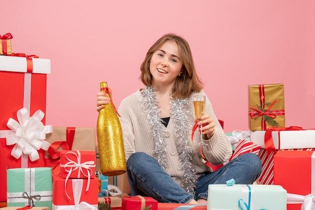Vorderansicht junge frau, die um weihnachtsgeschenke sitzt, die mit champagner feiern
