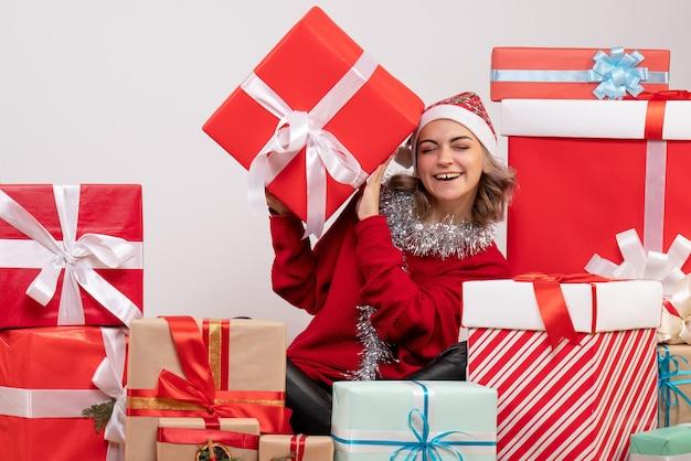Vorderansicht junge frau, die um weihnachtsgeschenke sitzt