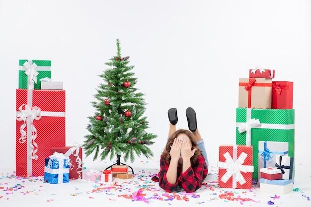 Vorderansicht junge frau, die um weihnachtsgeschenke und feiertagsbaum auf weißem hintergrund weihnachten neujahrsgeschenkfarbe schnee legt
