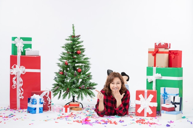 Vorderansicht junge frau, die um weihnachtsgeschenke und feiertagsbaum auf weißem hintergrundgeschenk weihnachten neujahrsfarbschnee legt
