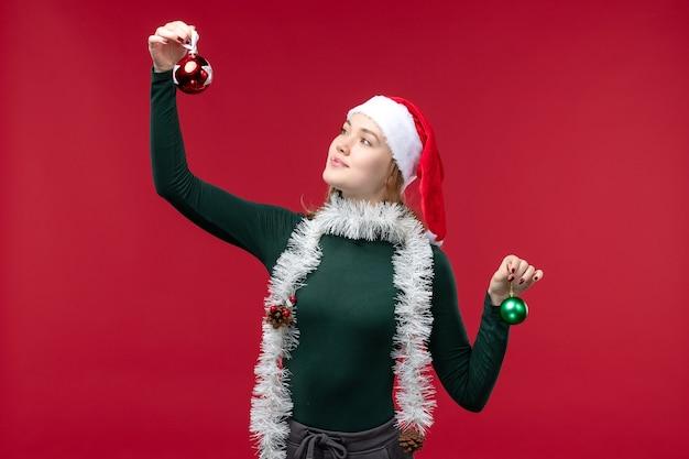 Vorderansicht junge frau, die weihnachtsbaumspielzeug auf dem roten hintergrund hält
