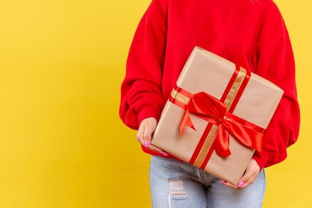Vorderansicht junge frau, die weihnachtsgeschenk auf gelbem hintergrund hält