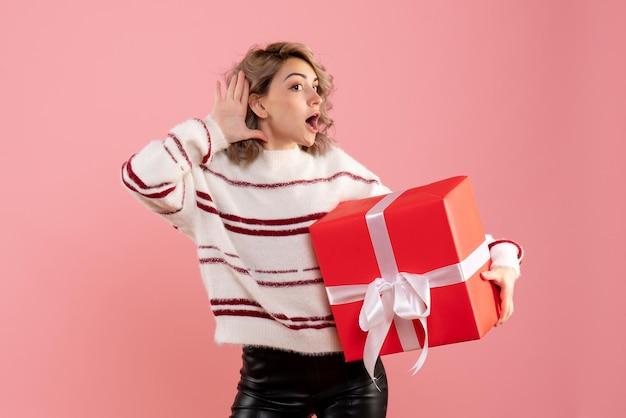 Vorderansicht junge frau, die weihnachtsgeschenk hält