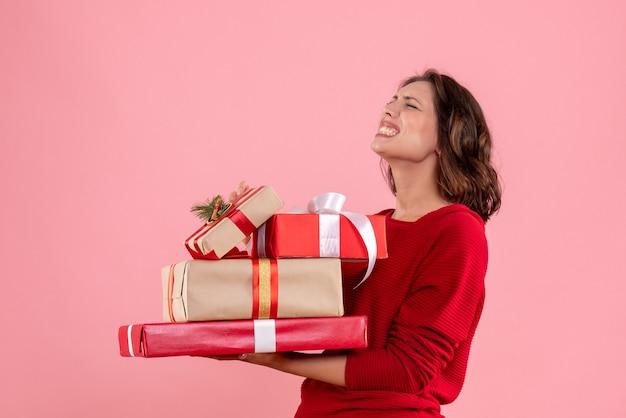 Vorderansicht junge frau, die weihnachtsgeschenke auf dem rosa trägt
