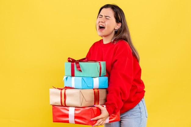 Vorderansicht junge frau, die weihnachtsgeschenke auf gelbem boden neujahrsmodellfarbe menschliches weihnachtsgeschenk hält