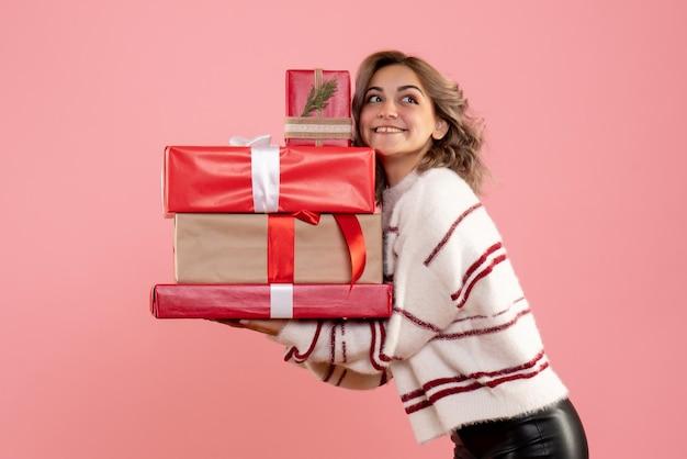 Vorderansicht junge frau, die weihnachtsgeschenke hält