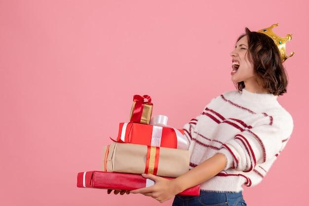 Vorderansicht junge frau, die weihnachtsgeschenke mit krone auf ihrem kopf auf rosa hintergrundfeiertagsfarbemotionsfrauenweihnachtsneujahr trägt