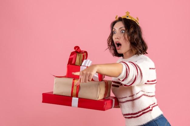 Vorderansicht junge frau, die weihnachtsgeschenke mit krone auf ihrem kopf auf rosa hintergrundweihnachtsfeiertagsemotion frau neujahrsfarbe trägt