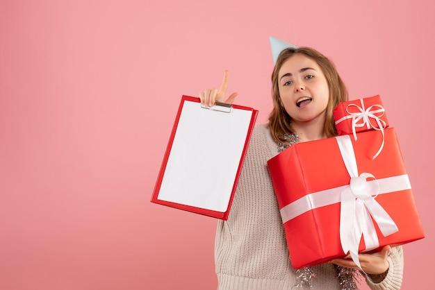Vorderansicht junge frau, die weihnachtsgeschenke und notiz hält