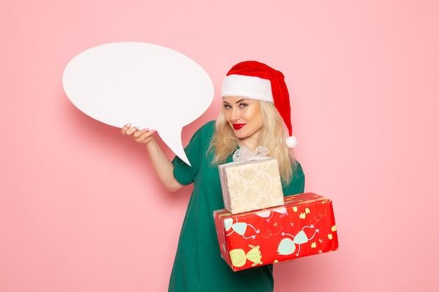 Vorderansicht junge frau, die weihnachtsgeschenke und weißes zeichen auf rosa wandfrau geschenk schneefarbfoto neujahrsferien hält