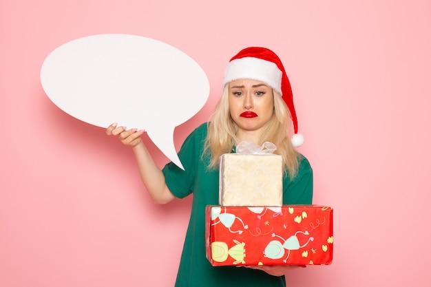 Vorderansicht junge frau, die weihnachtsgeschenke und weißes zeichen auf rosa wandfrauengeschenkschneefarbfoto neues jahr hält