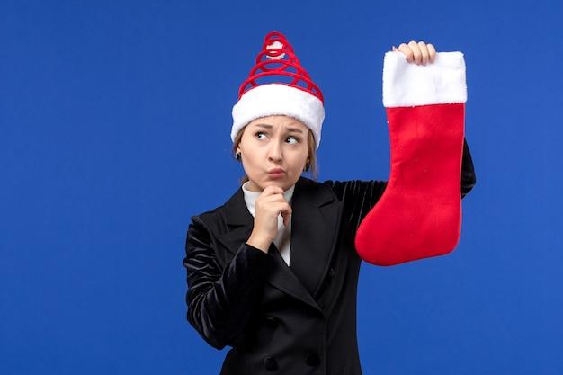 Vorderansicht junge frau, die weihnachtssocke auf dem blauen wandfeiertag neujahrsmensch hält