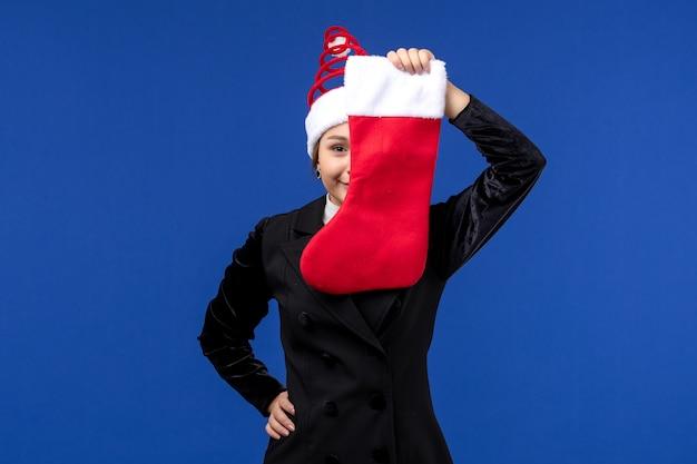 Vorderansicht junge frau, die weihnachtssocke auf neujahr der blauen schreibtischfeiertagsfrau hält