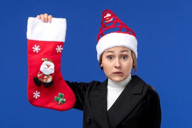 Vorderansicht junge frau, die weihnachtssocke auf neujahrsfeiertag der blauen wandfrau hält