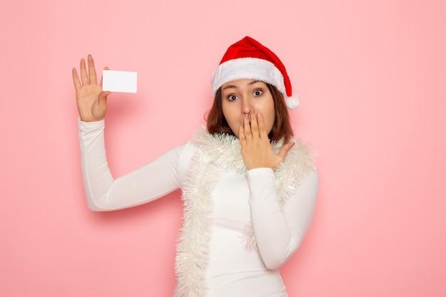 Vorderansicht junge frau, die weiße bankkarte auf der rosa wandweihnachtsfarbfeiertags-neujahrsmode hält
