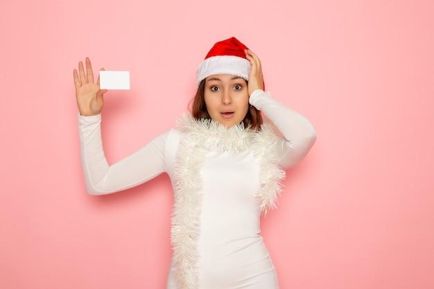 Vorderansicht junge frau, die weiße bankkarte auf rosa wandweihnachtsfeiertags-neujahrsfarbgeld hält