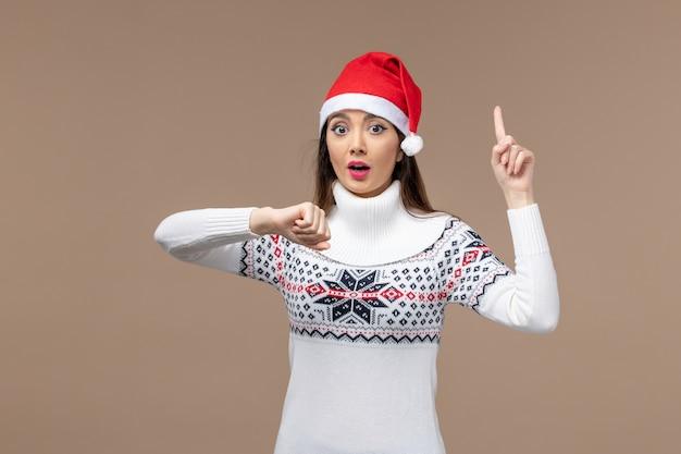 Vorderansicht junge frau, die zeit auf braunem hintergrund emotionen weihnachten neujahr prüft