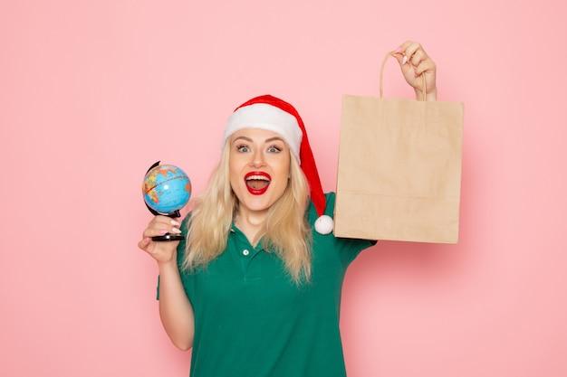 Vorderansicht junge frau hält globus und weihnachtsgeschenk auf rosa wandmodell frau weihnachten neujahrsfeiertag