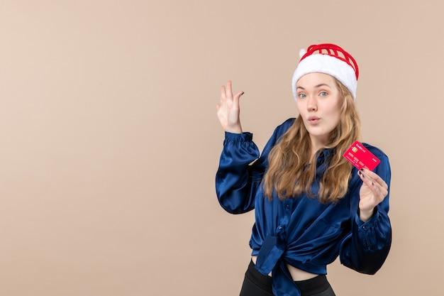 Vorderansicht junge frau hält rote bankkarte auf rosa hintergrund geld urlaub foto neujahr weihnachten emotion