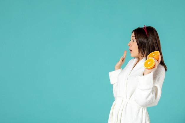 Vorderansicht junge frau im bademantel, die geschnittene orange auf blauem hintergrund hält