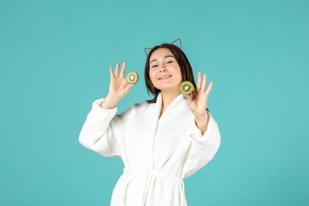Vorderansicht junge frau im bademantel mit geschnittenen kiwis auf blauem hintergrund Kostenlose Fotos