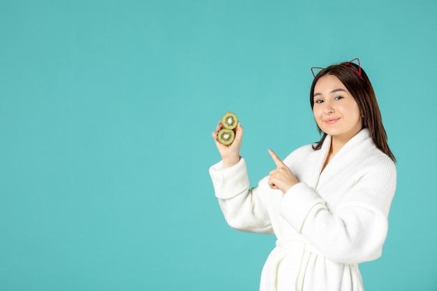 Vorderansicht junge frau im bademantel mit geschnittenen kiwis auf blauem hintergrund