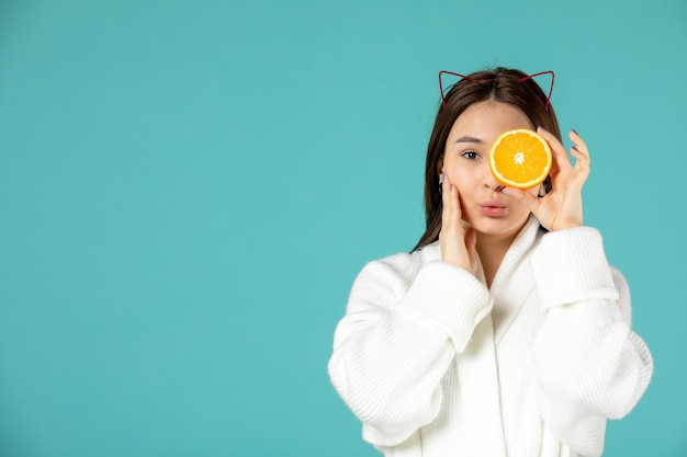 Vorderansicht junge frau im bademantel mit orangenscheibe auf blauem hintergrund