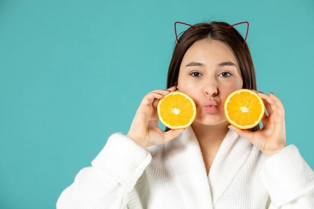 Vorderansicht junge frau im bademantel mit orangenscheiben auf blauem hintergrund