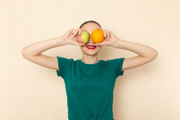 Vorderansicht junge frau im dunkelgrünen hemd und in den blauen jeans, die apfel und orange auf beige halten