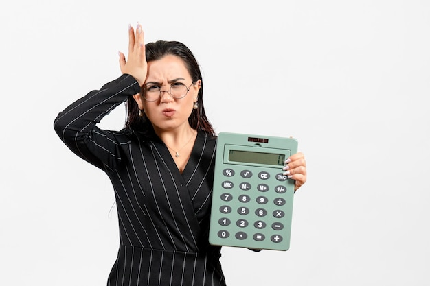 Vorderansicht junge frau im dunklen strengen anzug mit großem taschenrechner auf weißem hintergrund job beauty woman fashion business office