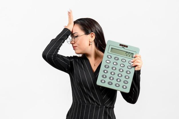 Vorderansicht junge frau im dunklen strengen anzug mit taschenrechner auf weißem hintergrund job frau büro mode business beauty