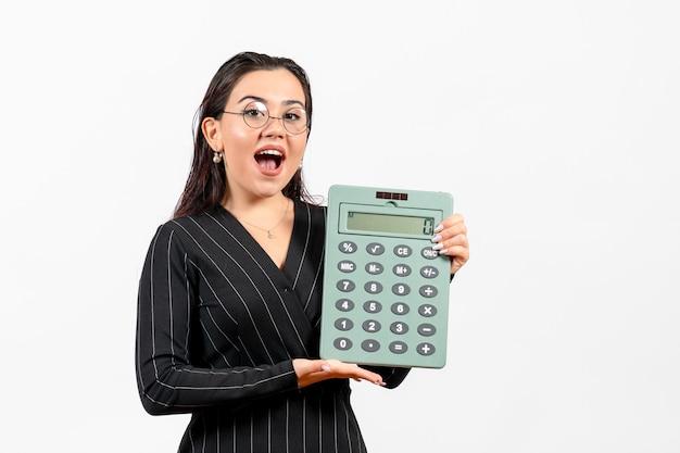 Vorderansicht junge frau im dunklen strengen anzug mit taschenrechner auf weißem hintergrund job frau mode business beauty office