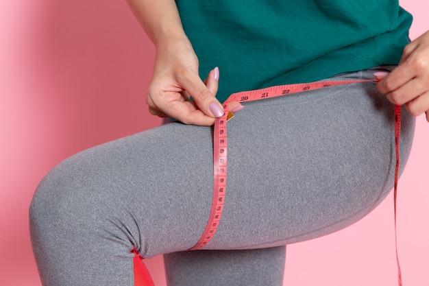 Vorderansicht junge frau im grünen t-shirt, das ihre größen auf der hellrosa wandtaille übung workout beauty schlanken weiblichen sport misst