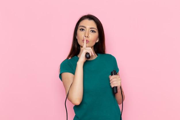 Vorderansicht junge frau im grünen t-shirt, das springseil auf der rosa wandtaille sporttraining workouts beauty slim athlet hält