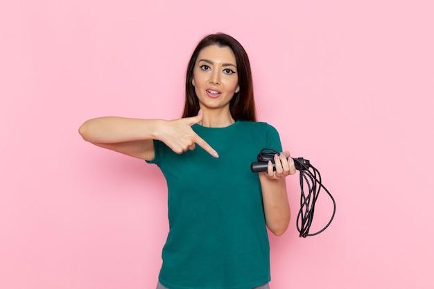 Vorderansicht junge frau im grünen t-shirt, das springseil auf der rosa wandtaille sportübung workout beauty slim athlet hält